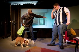 The man in the West Bromwich Albion shirt gestures with his hands putting a claw like muzzle to his face. Troy is trying to convince Bubble to take the dog.