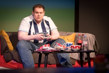 The young man looks like he does not do exercise. He is big and he wears a West Bromwich Albion football shirt, he sits on the sofa holding a game controller; he is surrounded by empty Crisp packets, bottles of Coke, Dr Pepper and old cups of tea. The character is known as Bubble