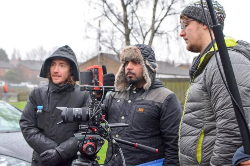 Three men stand, they wrapped up in coats. They are using a camera on a tripod.