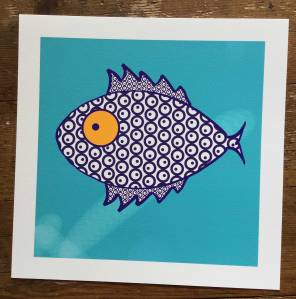 A monochrome blue and white 2D silhouette of a fish facing to the left. The fish has a large round orange eye with a blue dot as a pupil. The fish has both dorsal and pelvic fins both in the shape of mohawk and a small tail fin. The fish is patterned with circles and each circle has a dot within the circle. The dorsal and pelvic fins are also patterned with circles and dots, but these are much smaller. The fish is painted onto a plain turquoise background with a white boarder. The painting is placed on dark wooden boards.