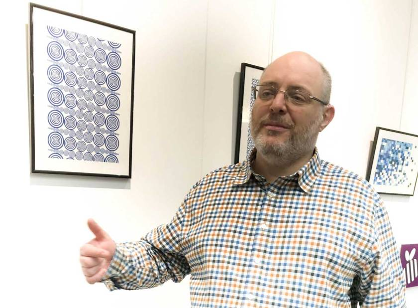 Man with Patterned shirt Stands in front of picture Hung on White wall